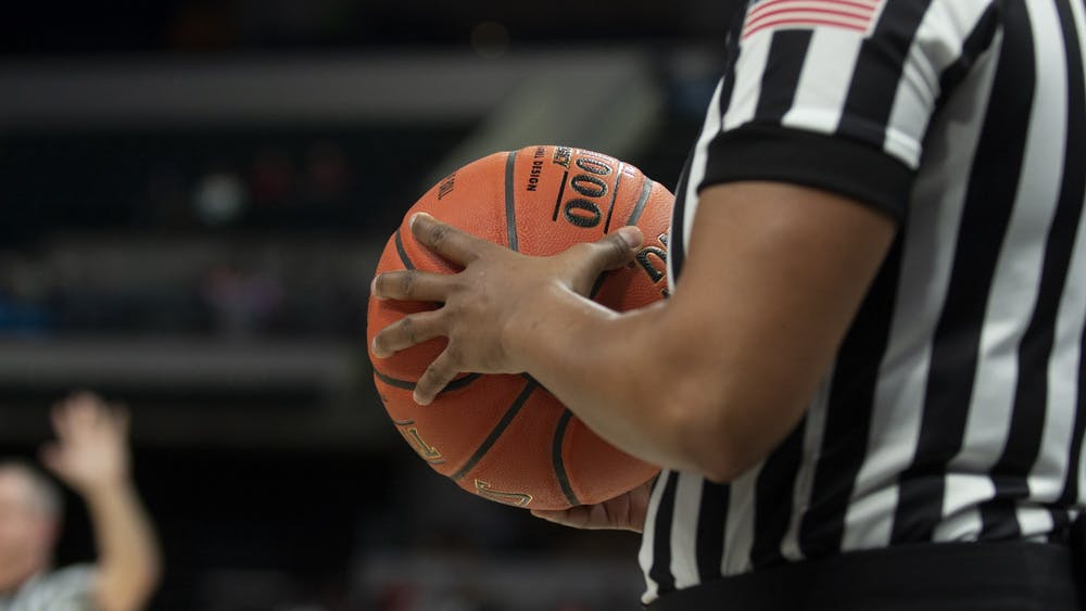 A referee holds a basketball at the Big Ten Tournament on March 6 at Bankers Life Fieldhouse in Indianapolis. The NCAA announced Monday the 2021 men's basketball tournament will be held at one geographic location, with the state of Indiana and the Indianapolis metropolitan area being the likely location.