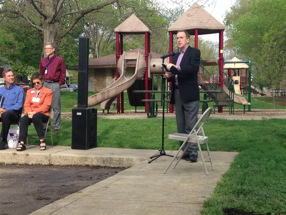 Bloomington Mayor Mark Kruzan presents at the unveiling of a new interpretive sign Monday evening at Building and Trades Park.