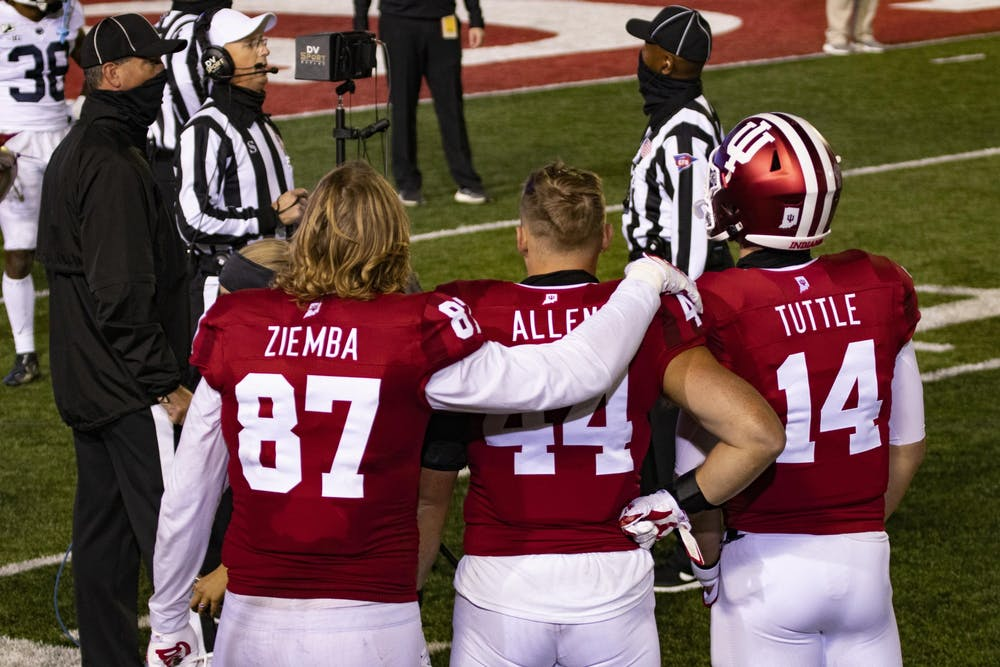 <p>Senior defensive lineman Michael Ziemba puts his arm around redshirt junior linebacker Thomas Allen with redshirt sophomore quarterback Jack Tuttle on Oct. 24 in Memorial Stadium. The IU football players watched as the referee confirmed the final touchdown in double overtime  against Penn State University.</p>