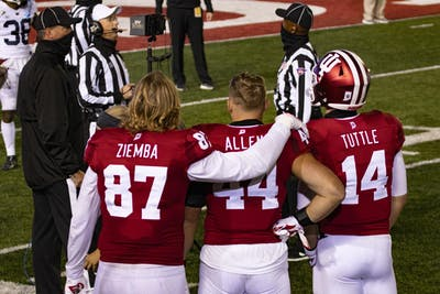 Senior defensive lineman Michael Ziemba puts his arm around redshirt junior linebacker Thomas Allen with redshirt sophomore quarterback Jack Tuttle on Oct. 24 in Memorial Stadium. The IU football players watched as the referee confirmed the final touchdown in double overtime  against Penn State University.