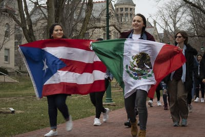 "Students Christina Colón and Angelica Navarro chant, ""There is more that unites us than divides us,"" during the Latinx IUnity Walk on March 21. The core message of the walk is to promote inclusiveness of all IU students, as well as unify all Latino communities and organizations on campus."