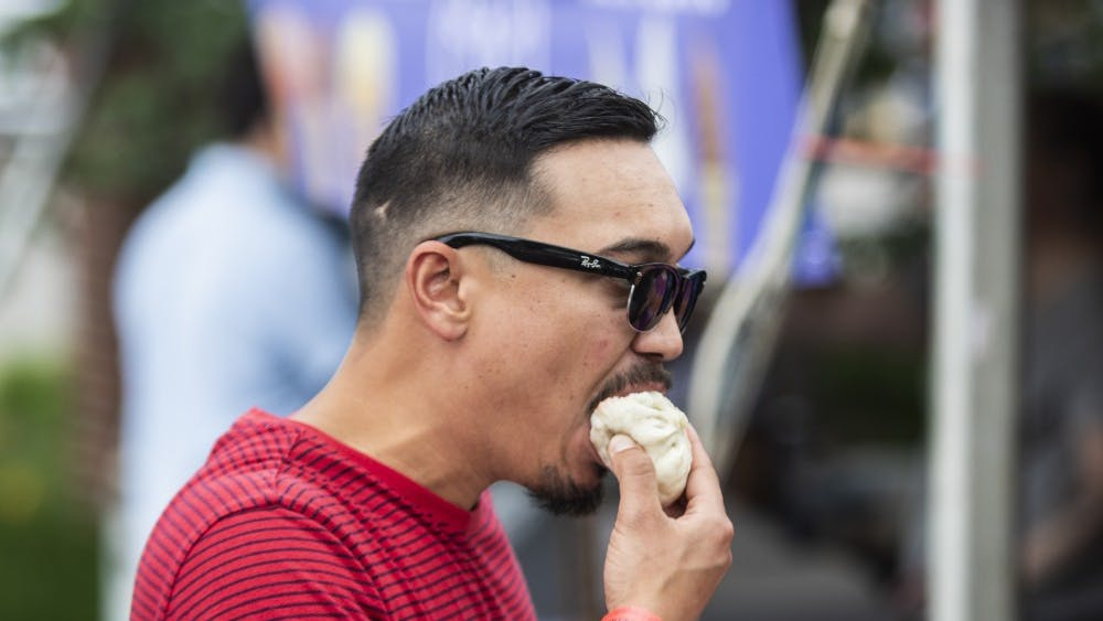 "Bloomington resident Brandon Panganiban eats a meat bun from Oasis Chinese's booth June 22 at the Taste of Bloomington. ""I'm here for the food,"" he said."