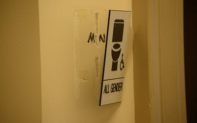 A gender-neutral bathroom sign on the third floor of the Student Building was ripped partially from the wall Tuesday.