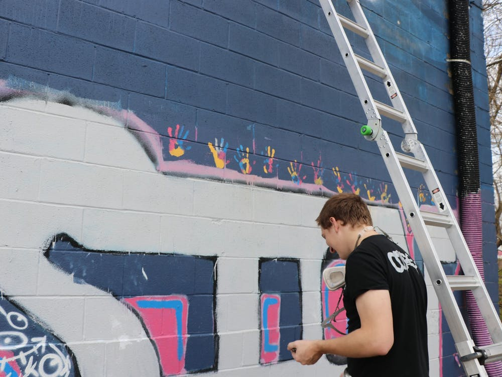 Sophomore Trenton Musch works on his mural Nov. 20 outside of The Warehouse in Bloomington.