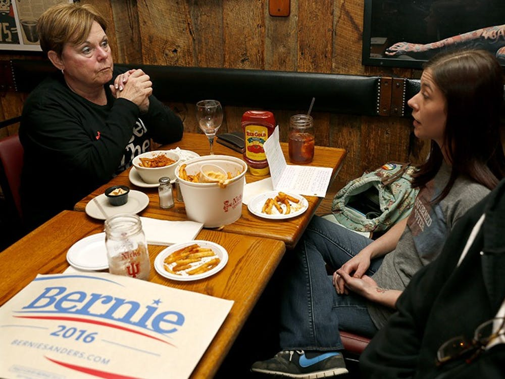 Ruth Simcox, left, Jessica Martlage, and Shellie Martlage talk before the CNN Democratic debate begins Wednesday at the Nick's English Hut. Bloomington Bernie Supporters opened a group meeting to watch the debate and support Bernie Sanders.