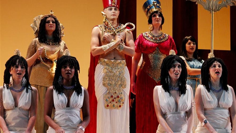"""Akhnaten, played by Nicholas Tamagna, is flanked by Nefertiti, played by Sarah Ballman, and Queen Tye, played by Olivia Savage, in a pre-opening staging of Philip Glass' """"Akhnaten"""" Tuesday evening at the IU Musical Arts Center. Akhnaten is the first collaboration production between the IU Opera & Ballet Theater and the Indianapolis Opera."""