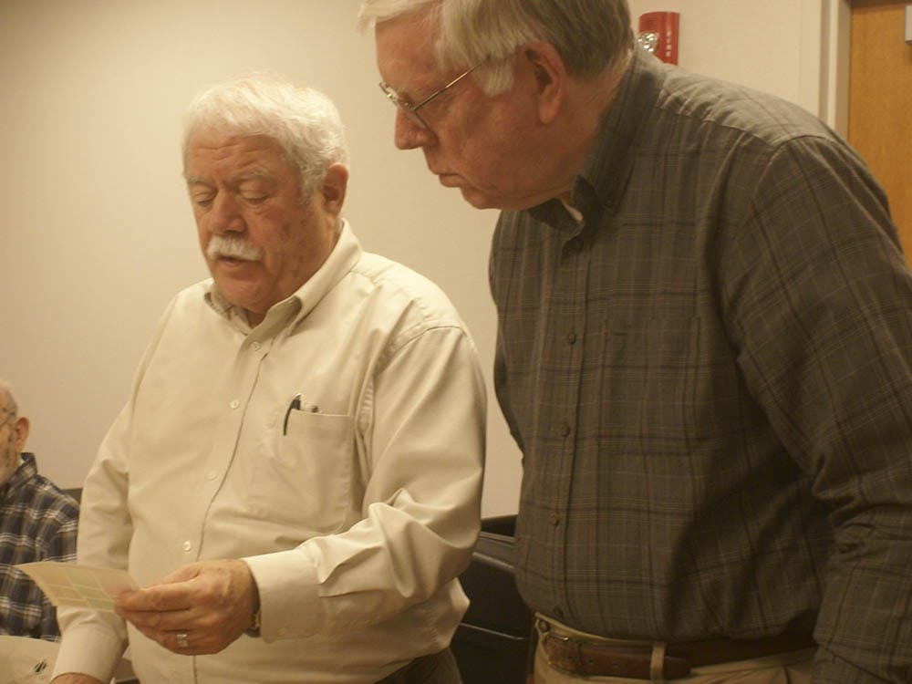 Mark Goodson and Doug Tracy look at stamps they will organize for the members at next month's meeting Wednesday evening at the Monroe County Public Library. The members have the option to trade and buy stamps from each other at each meeting.
