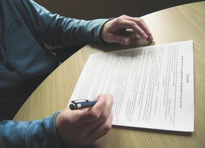 A student signs a lease. Many students sublease their homes during the academic year to study abroad or graduate early.