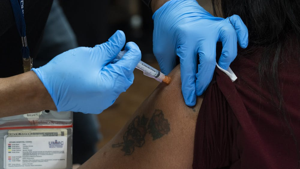 A health care worker is injected with the Moderna COVID-19 vaccine Dec. 21, 2020, at United Memorial Medical Center in Houston, Texas.