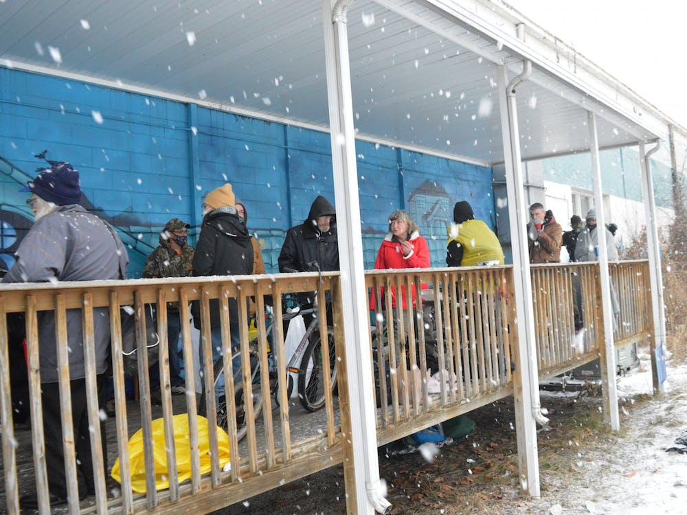 Members of the homeless community gather until the doors of A Friend's Place open at 5:15 p.m. Saturday. They stood under the porch of the shelter to avoid the snow.