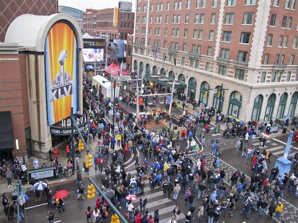 Attendees walk through the rain Jan. 4 at the Super Bowl Village in Indianapolis. Local businesses reported an increase in customers the week before the game.