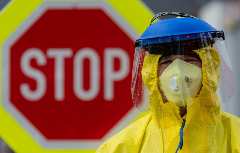 A firefighter in protective clothing stands in front of a stop sign March 11 during a check of travelers at a petrol station on the D8 Dresden-Prague motorway. To prevent the coronavirus from spreading, the Czech Republic has started random checks of travelers at the borders to Germany and Austria.