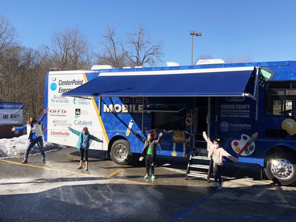 <p>A MCCSC faculty member and students pose for a photo in front of the the STEM to THEM mobile lab. MCCSC introduced the new STEAM mobile classroom, which has color-coded lab stations, whiteboard cabinets, three TV monitors and robots. </p>