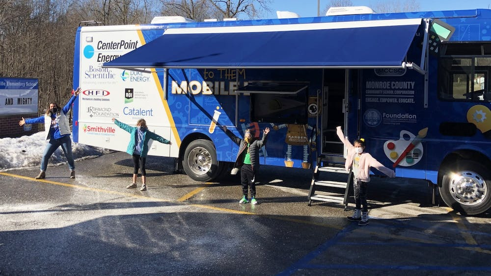 A MCCSC faculty member and students pose for a photo in front of the the STEM to THEM mobile lab. MCCSC introduced the new STEAM mobile classroom, which has color-coded lab stations, whiteboard cabinets, three TV monitors and robots.