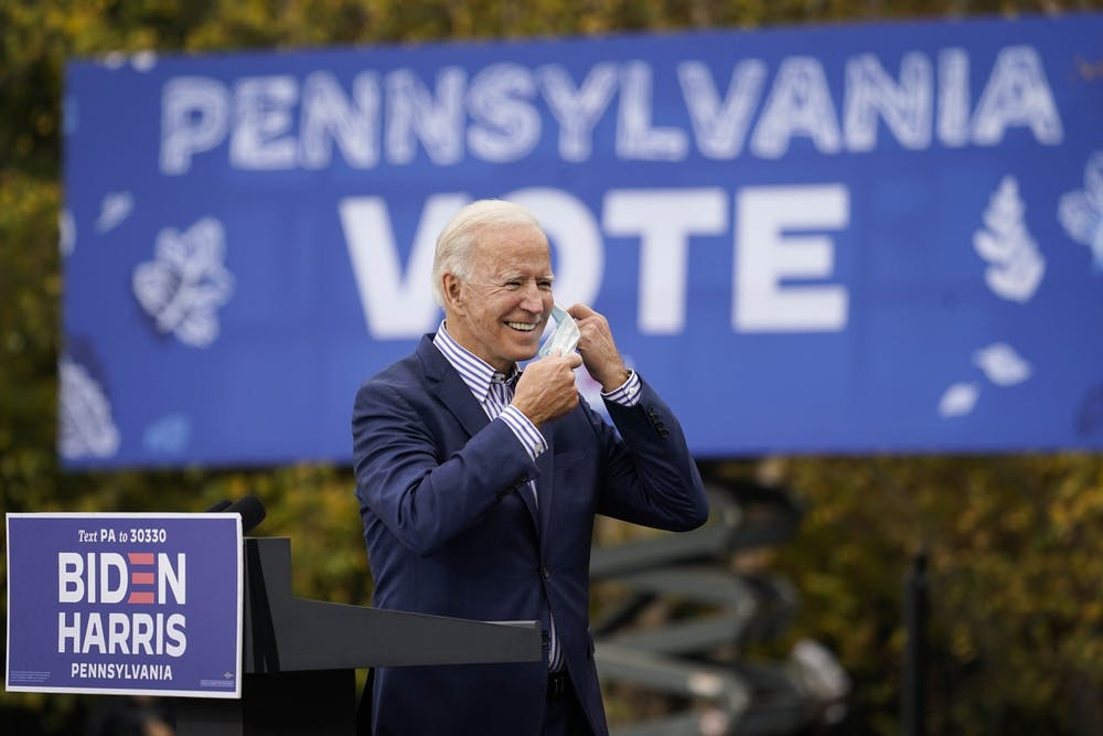<p>Then-Democratic presidential nominee Joe Biden takes off his face mask to speak during a drive-in campaign rally Oct. 24 at Bucks County Community College in Bristol, Pennsylvania. </p>