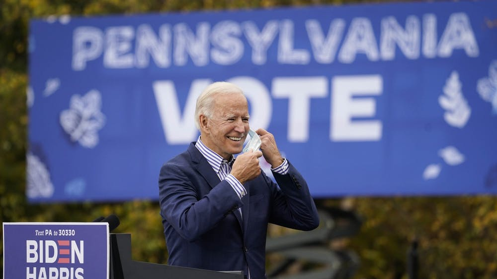Then-Democratic presidential nominee Joe Biden takes off his face mask to speak during a drive-in campaign rally Oct. 24 at Bucks County Community College in Bristol, Pennsylvania.