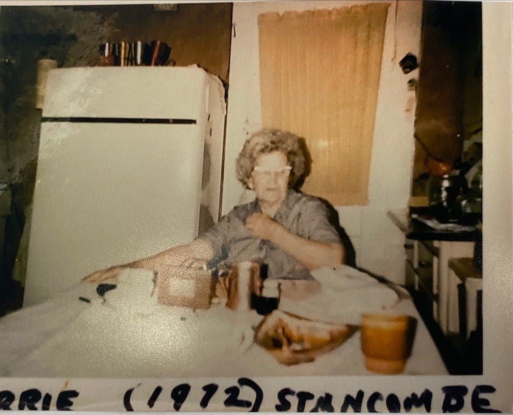 Carrie Stancombe sits at the dining room table of her house in 1972 at 523 W. 7th St. Aluminum cups can be seen on top of the fridge, and they would rattle when people walked in.