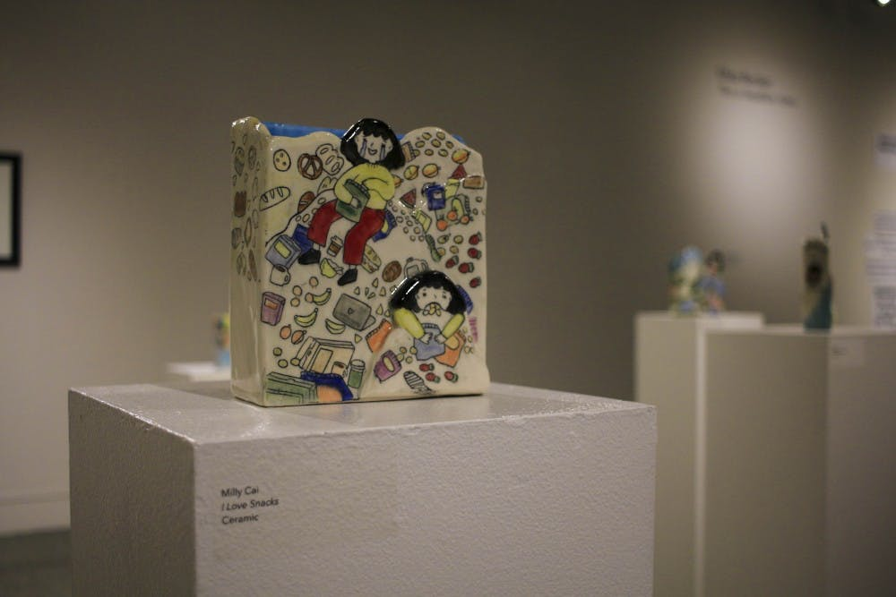 "<p>""I Love Snacks"" is a collection of drawings imposed on the flat surfaces of ceramic works by senior Milly Cai. The work is on display in the Grunwald Gallery.</p>"
