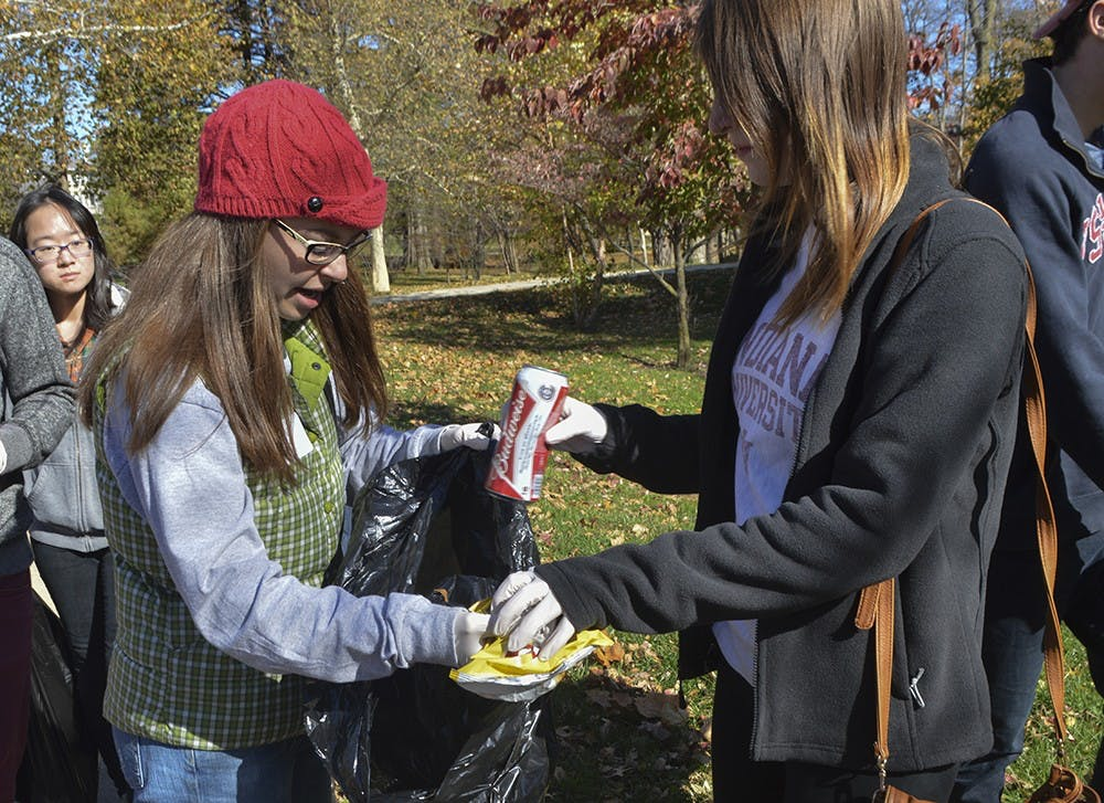Junior Shelby Fletcher holds the trash bag for Sophomore Lauren Daas as they clean up Sunday near Franklin Hall as part of the Civic Leadership Development Campus Cleanup.