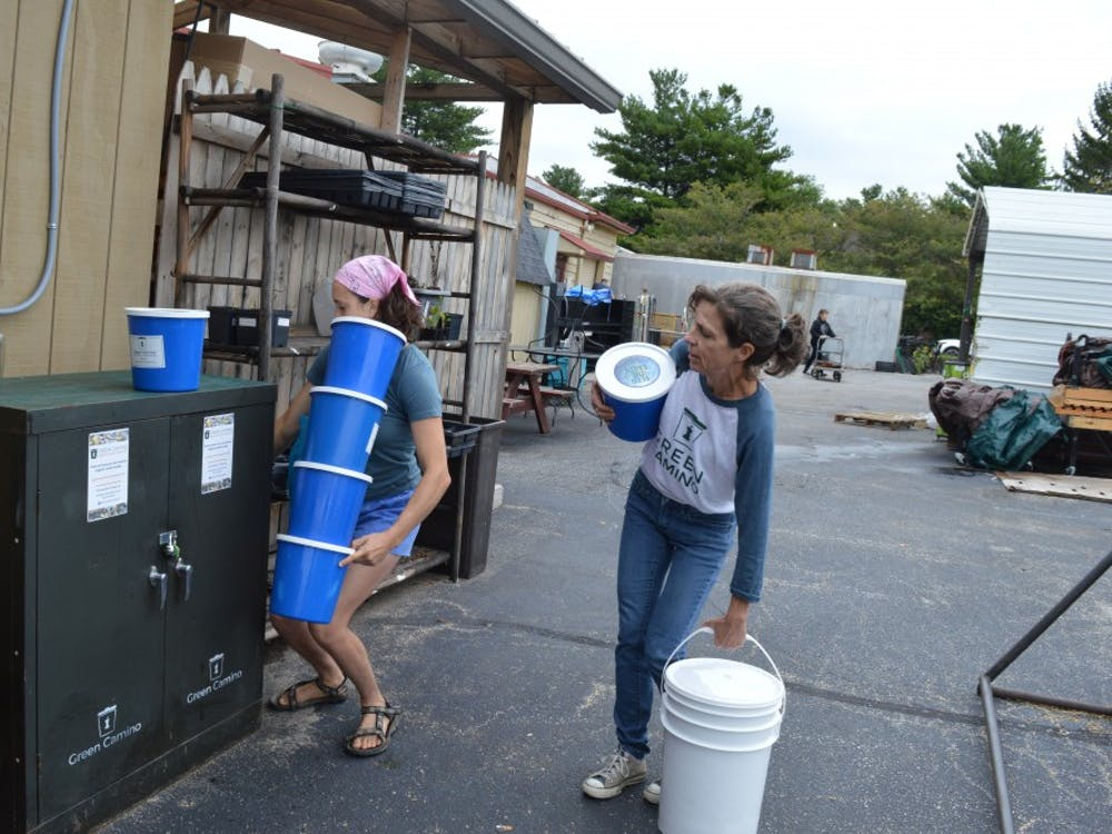 Green Camino, a curbside composting company, co-founder Kathy Gutowsky and employee Maggie Gates take empty pails from the drop off site next to Bloomingfoods East. Green Camino washes every pail by hand, and customers receive a clean one each time.