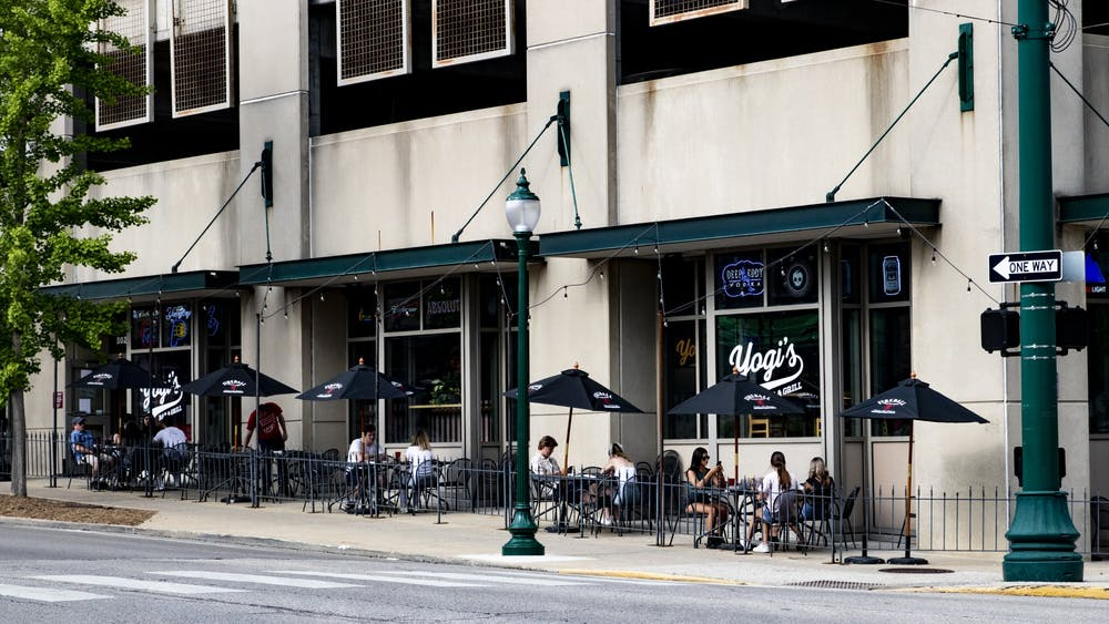 People sit outside of Yogi's Bar and Grill on May 16 along Walnut Street. Multiple restaurants in Bloomington have expanded outdoor seating to encourage social distancing.