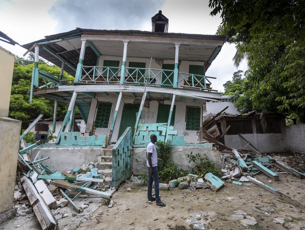 <p>A man stands in front of a damaged school in Corail, Haiti, on Aug. 19, 2021. Many structures in this small fishing village were damaged or destroyed by the earthquake. </p>