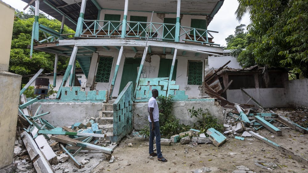 A man stands in front of a damaged school in Corail, Haiti, on Aug. 19, 2021. Many structures in this small fishing village were damaged or destroyed by the earthquake.