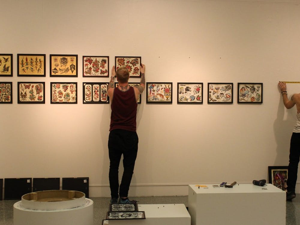 """Gallery technicians Erik Probst, left, and Clayton Blackwellhang tattoo flash sheets on a wall of the Grunwald Gallery. The gallery is opening its newest exhibition, """"Indiana Tattoo: History and Legacy,"""" on Friday."""