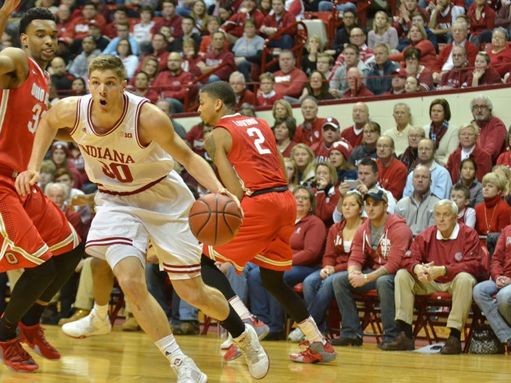 Then Junior forward Collin Hartman runs around an Ohio State defender on Sunday at Assembly Hall.