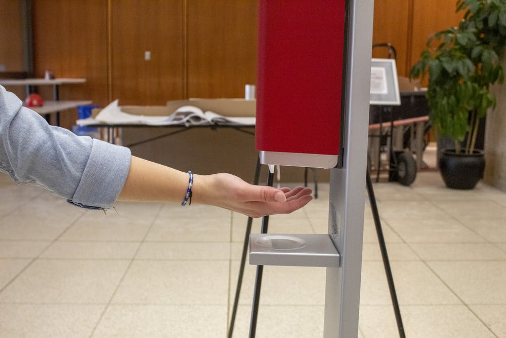 <p>Sophomore Macy Colson sticks her hand under a hand sanitizer station Aug. 23 in Herman B Wells Library. The library has installed multiple hand sanitizer stations around the building as a safety precaution against the coronavirus.</p>