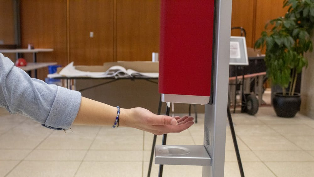 Sophomore Macy Colson sticks her hand under a hand sanitizer station Aug. 23 in Herman B Wells Library. The library has installed multiple hand sanitizer stations around the building as a safety precaution against the coronavirus.