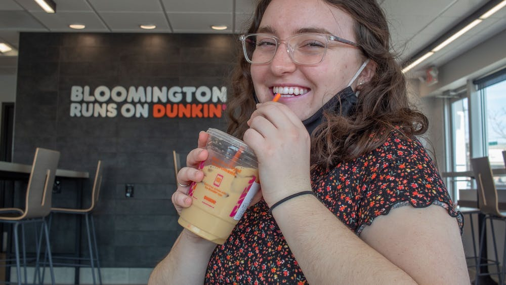 Freshman Kathleen Simunek sips on a small iced latte from Dunkin' on Monday. The Bloomington location opened Dec. 7, 2020.