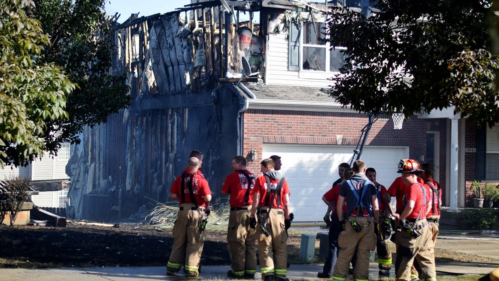 Firefighters assess the damage to 3541 S. Wickens St. after a fire broke out. Three houses suffered at least 80% damage, according to the Monroe Fire Protection District public information officer.