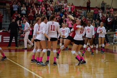 Kamryn Malloy lifts Bayli Lebo up in the air in joy as the rest of the team rushes to celebrate its victory against Ohio State on Oct. 19 in University Gym. IU swept Ohio State, 3-0.
