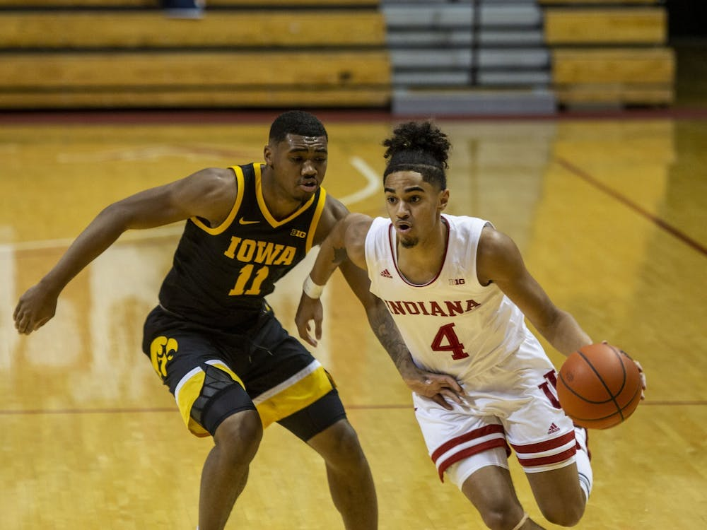 Freshman guard Khristian Lander dribbles the ball up the court on Feb. 7 at Simon Skjodt Assembly Hall. Lander announced Monday that he will withdraw from the transfer portal to remain at IU.