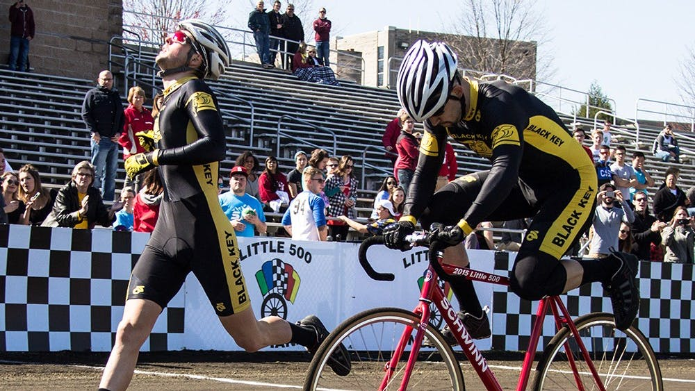Black Key Bulls riders Charlie Hammon and Spencer Brauchla exchange bike during the qualification on Saturday at Bill Armstrong Stadium. BKB will start the Little 500 race from the third place position with time 2:19.958.
