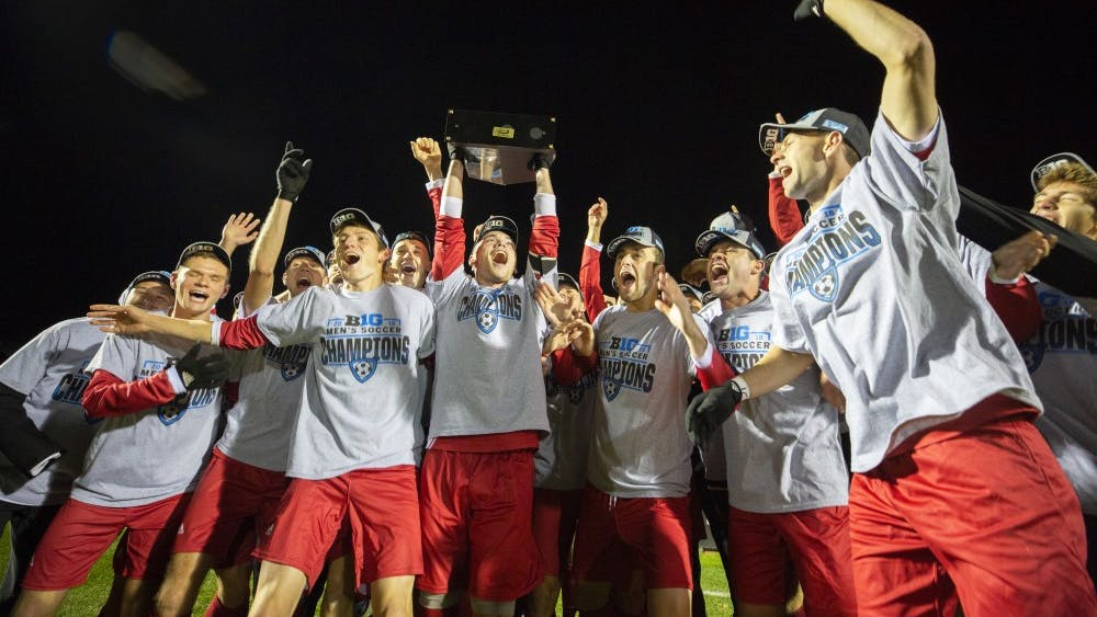 Members of the IU men's soccer team celebrate with the trophy after winning the Big Ten regular season title Oct. 24 at Jesse Owens Memorial Stadium. IU secured the title after defeating Ohio State University, 1-0. Senior defender Andrew Gutman scored the only goal of the night.