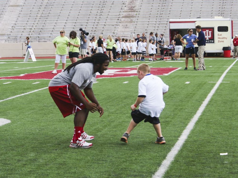 IU football running back Devine Redding plays defense against a child during the Change the Play event Tuesday in Bloomington.