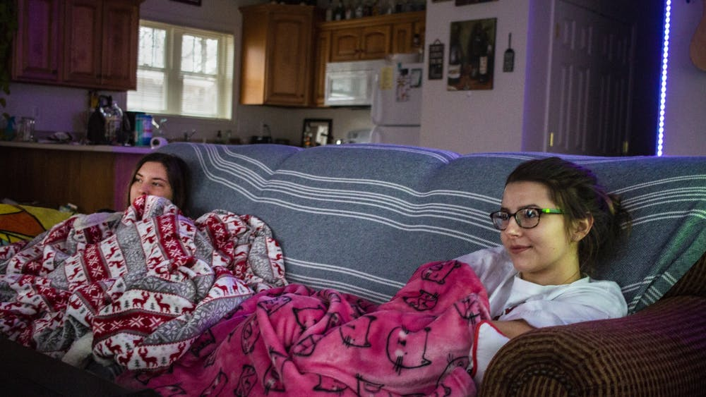 Juniors and roommates Skye Huffman, left, and Haley Leffler sit on their couch Jan. 12 in their off-campus house. If you decide to live with others, it's important to find people who you get along with.