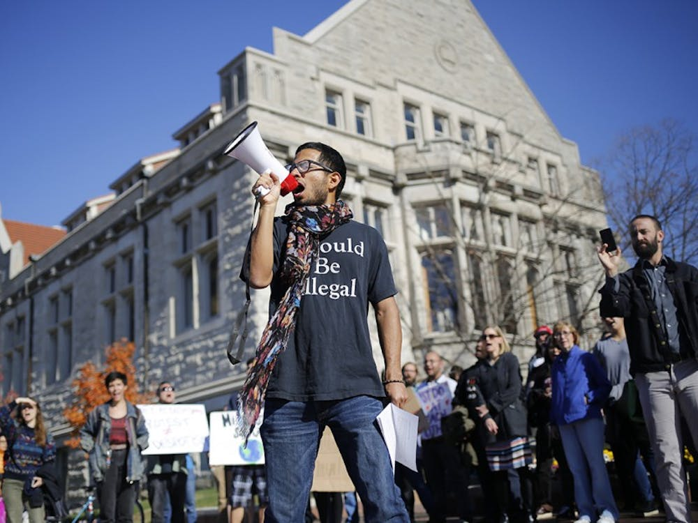 """Willy Palomo yells into a megaphone while leading a group of students in a chant during a rally for a Sanctuary Campus Wednesday at Sample Gates. Palomo is with the UndocuHoosier Alliance and was rallying to bring awareness to isues facing undocumented students on IU's campus. """"Hoosier Promise,"""" he yelled. """"Is a lie,"""" the crowd followed up. """"Only true,"""" he yelled out again. """"If you're white,"""" the crowd finished."""
