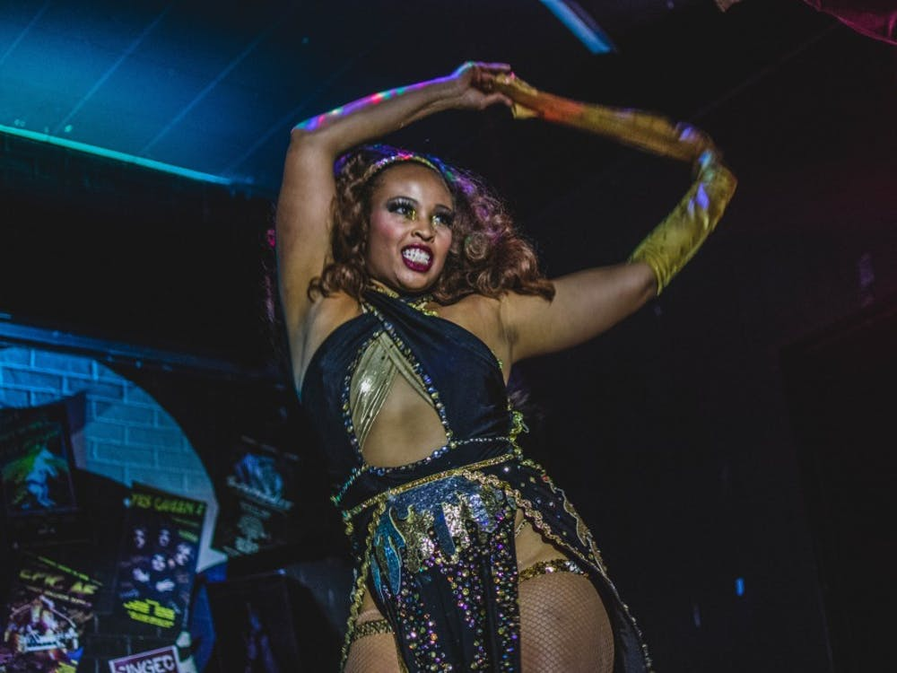 """Twirlisha Devine peels off one of her gloves during her routine at """"Singe's Summer Simmer"""" on July 20 at the Back Door. Devine also hosts """"Showgirl Sunday Dinner"""", a bi-weekly burlesque podcast."""