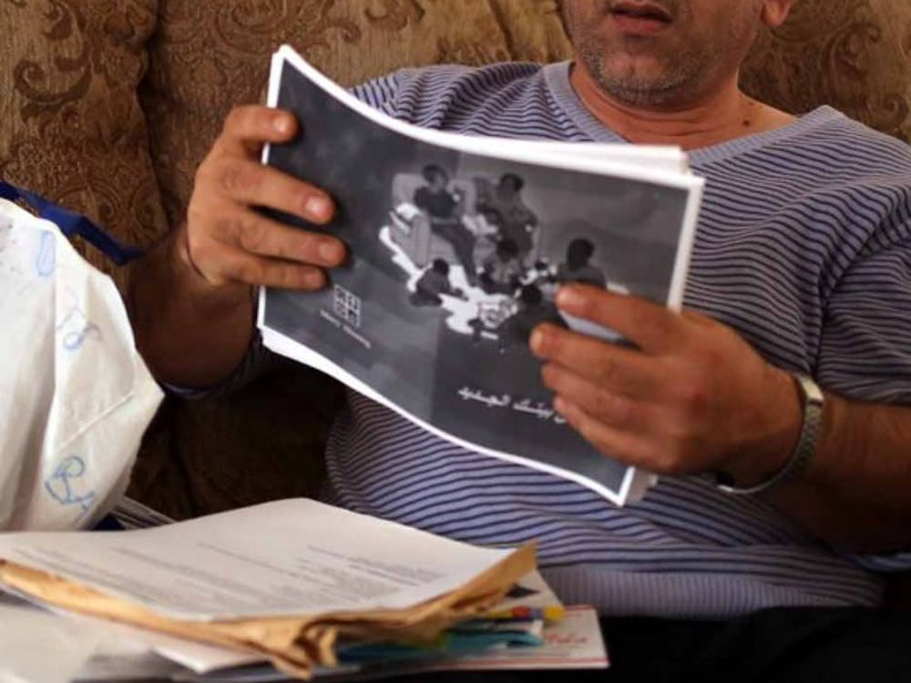 Marwan peruses through his bag of refugee documents - dozens of papers that overflow onto his lap that document his pathway to creating a new life for his family.