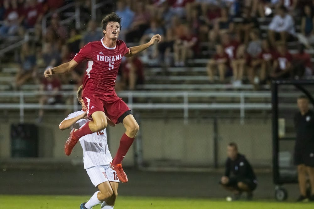 <p>Redshirt-junior defender Daniel Munie jumps for the ball Sept. 17, 2021, at Bill Armstrong Stadium. Munie earned his second Big Ten Defensive Player of the Week award.</p>