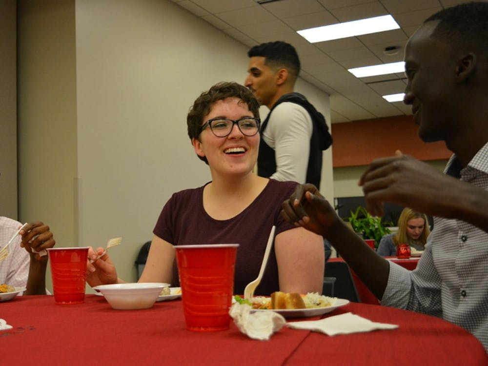 """Junior Mohamed Abdirisak,freshman Becca Karstensen and senior Mohamed Mohamed laugh during aconversation at the """"Taste of Islam"""" banquet. Students were invited to come learn about the culture of food in Muslim-majority countries at the Islam Awareness week event."""