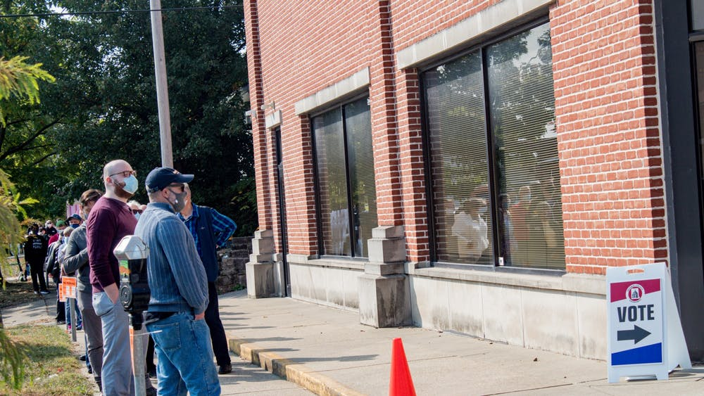 Voters wait in line to vote Oct. 6 at 401 W. Seventh St.