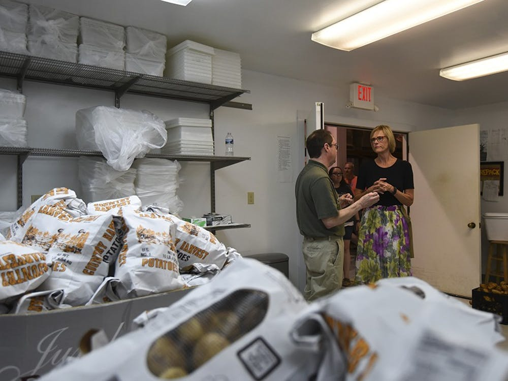 While volunteers from Farm Credit Mid-America bag pototoes, Suzanne Crouch and Julio Alonso discuss how fresh fruits and vegetables are donated to the food bank. Many local farmers from the Bloomington Farmer's Market contribute food.