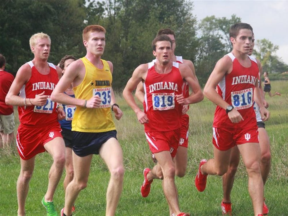 A pack of runners from the IU men's cross country team strides around the corner at the season opener Saturday at the IU Cross Country Course.