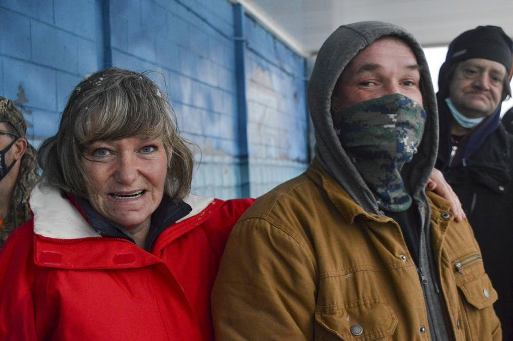 <p>Candance Goffinet, 50, and Jason Oliphant, 47, wait outside A Friend's Place Saturday. The doors opened at 5:15 p.m. and members of the homeless community gathered together until it opened.</p>