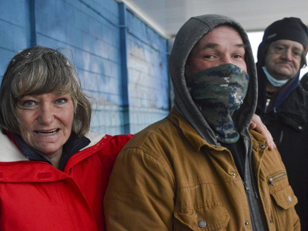 Candance Goffinet, 50, and Jason Oliphant, 47, wait outside A Friend's Place Saturday. The doors opened at 5:15 p.m. and members of the homeless community gathered together until it opened.