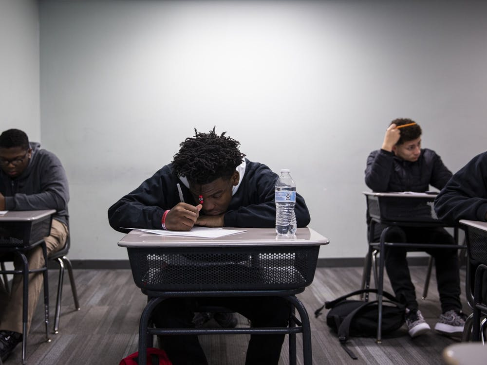 Da'Quincy Pittman copies down notes in geometry class. He learned how to find the volume of a sphere before heading back to Fama's office to rest. The nerves in his foot were aching, as they often do.